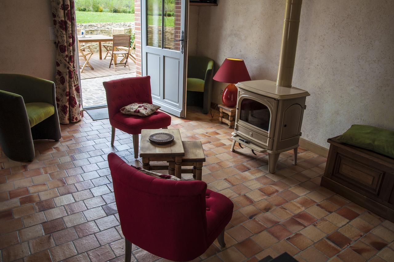 Un espace salon autour d'un poële à bois, ouvert sur la cuisine et la salle à manger